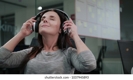 A young lady putting on headphones and listening to music indoors. Medium shot. Soft focus
