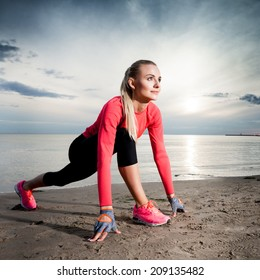 Young lady ready to run on a beach during sunset