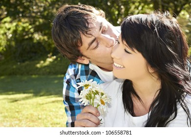 Young lady receives flowers from young man while he kisses her on the cheek