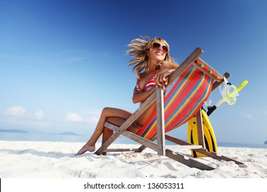 Young lady relaxing in a chair on a tropical beach with white sand