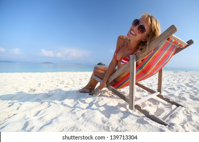 Young lady relaxing in a chair on a beach at sunny day