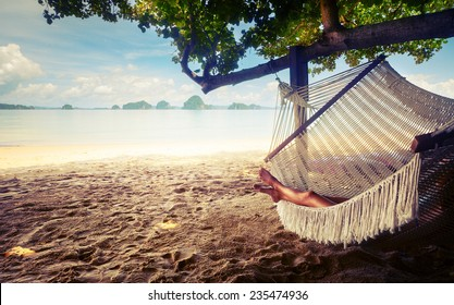 Young lady relaxing in the hammock on the sandy beach with view on remote tropical islands