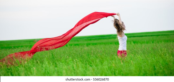 Young lady runing with tissue in green field. Beautiful happy woman walking  in the summer rural meadow. Outdoor summer portrait of pretty sport style woman jumping with fabric. Beautiful fit tan girl