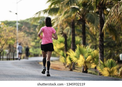 Young lady running on a asphalt road in the morning
