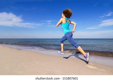 Young lady running on a beach at the seaside