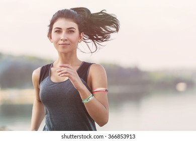 Young lady running on a beach during morning with wearable devices