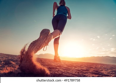 Young lady running on the desert at sunset