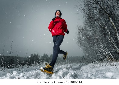 Young lady running in snowy winter forest