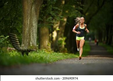 Junge Dame läuft. Frauenläufer, die durch die Frühlingsparkstraße rennen. Training in einem Park. Schönes Mädchen. Fitnessmodell im Freien.Gewichtsverlust