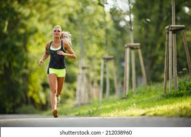 Junge Dame läuft. Frauenläufer, die durch die Frühlingsparkstraße rennen. Training in einem Park. Schönes Mädchen. Fitnessmodell im Freien. Gewichtsverlust