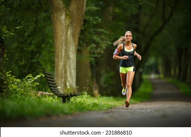 Young lady running. Woman runner running through the spring park road. Workout in a Park. Beautiful fit Girl. Fitness model outdoors. Weight Loss
