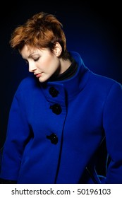 Young lady with short hair dressed in a blue topcoat