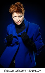 Young lady with short hair dressed in a blue topcoat and black gloves