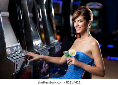 young lady sitting by the slot machine, posing with cocktail