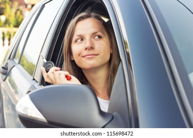 Young lady sitting in a car and showing key