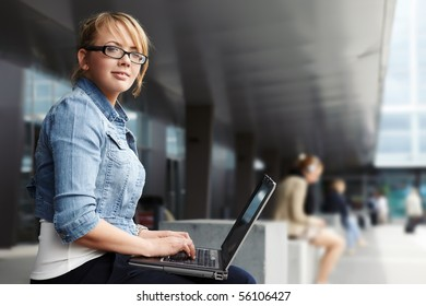 Young lady sitting in a modern cityscape with laptop