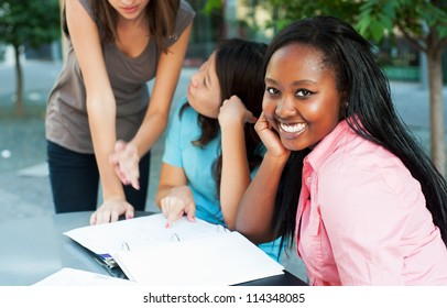 Young lady smiling at camera while friends study in background