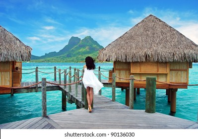 Young lady stand alone , look towards to the Otemanu mountain at Bora Bora island , French Polynesia , Pacific ocean .