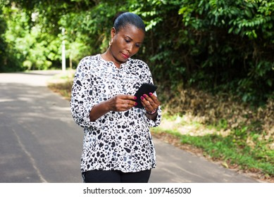 young lady standing in black white shirt in street looking at her mobile phone smiling.
