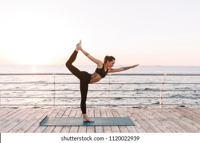 Young lady standing and training yoga poses by the sea. Pretty woman in black sporty top and leggings practicing yoga with beautiful sea view on background