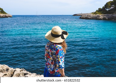 A young lady in a straw floppy hat standing on the edge of the cliff and looking at the horizon.