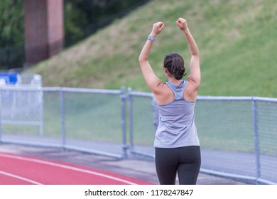 A young lady is stretching her arms while walking