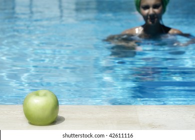 young lady swimming to an apple in the corner of the pool