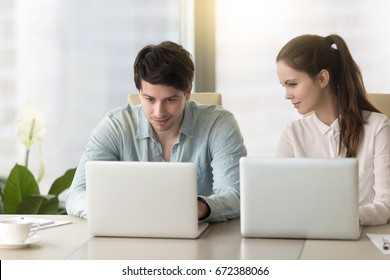 Young lady taking inquisitive glance, sneak peek at laptop screen of male colleague, stealing private information from computer of competitor, nosy female coworker sitting next to man spying on him