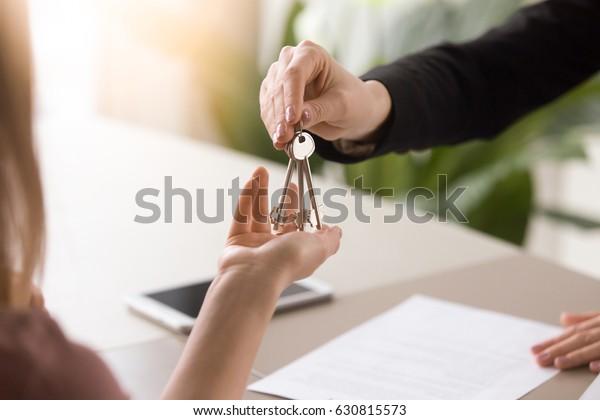 Junge Dame, die während der Sitzung nach der Unterzeichnung des Mietvertrags oder Kaufvertrags Schlüssel von weiblichen Immobilienmaklern abholt. Unabhängige Frau kauft neues Zuhause, Nahaufnahme
