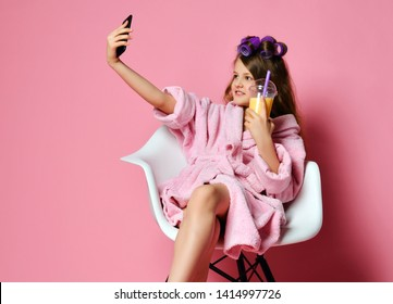 Young lady teen girl in bathrobe and with hair in curlers in beauty shop drinks smoothie fresh juice and have fun taking cool selfie. Beauty concept on pink background with text copy space
