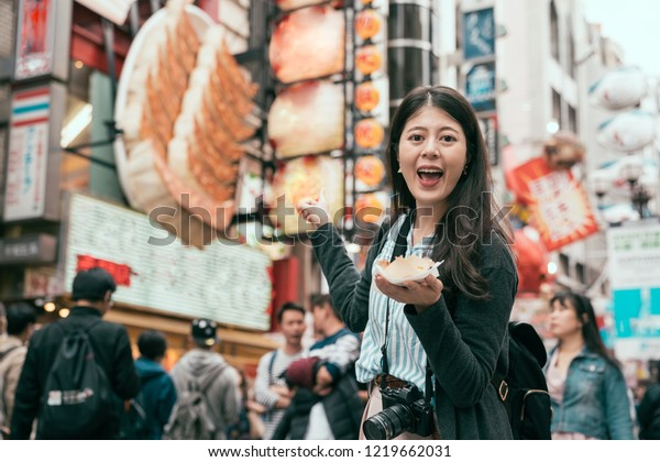 young lady traveler holding japanese street food. beautiful tourist standing in front of the dumpling store in dotonbori. enjoy osaka travel lifestyle.