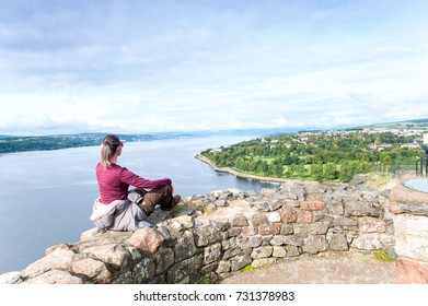 Young lady traveller sitting on top of rock cliff making picture of panoramic view by smartphone on blue sky background. Summertime colorful horizontal image. Uk, Scotland, Glasgow area, Dumbarton.