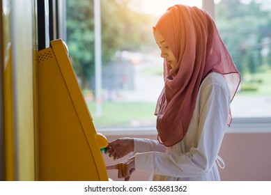 Young lady using an automated teller machine . Woman withdrawing money or checking account balance.