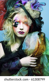 Young lady as vintage doll in exotic hat and with bright make-up