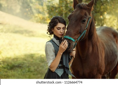 A young lady in a vintage dress, with tenderness and with affection hugs her horse. An ancient, collected hairstyle, a gentle make-up. Background of summer fields. Art photo