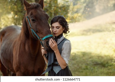 A young lady in a vintage dresses with a long train, lovingly embraces her horse with tenderness and affection. An ancient, collected hairstyle, a gentle make-up. Background summer forest glade.