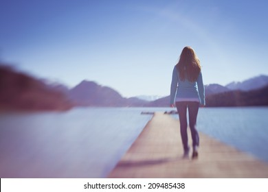 Young Lady Walking Away on Small Lake Wooden Space Path