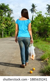 A young lady walking in the with a broken shopping bag, and some oranges dropped in the street.