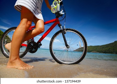 Young lady walking on a beach with bicycle and with snorkeling equipment at sunny day