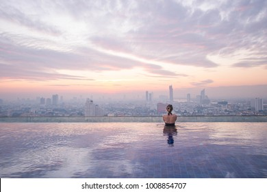 Young lady watching the sunrise at the infinity pool with city view. Bangkok, Thailand.