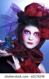 Young lady witn bright make-up in doll-style with glass box and beads in it