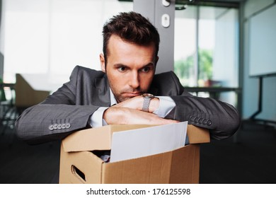 Young laid off manager sitting down with a carton