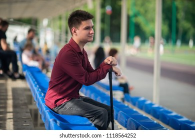 Young lame man sitting in the stadium