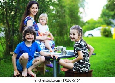 A young large family at a picnic on a summer morning. A beautiful mother with children is having breakfast in the park.