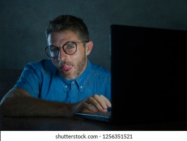 young lascivious and aroused porn addict man in nerd glasses watching sex movie online late night at laptop computer looking pervert and horny in internet pornography and sex content