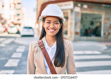 Young latin architect girl smiling happy standing at the city.