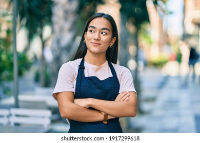 Young latin barista girl with arms crossed smiling happy at the coffee shop
