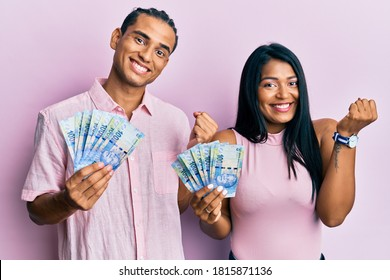 Young latin couple holding south african rand banknotes screaming proud, celebrating victory and success very excited with raised arm