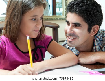 Young latin father helping her daughter with her homework