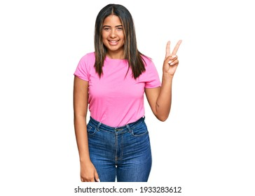 Young latin girl wearing casual clothes smiling with happy face winking at the camera doing victory sign. number two.